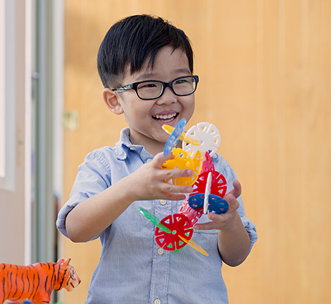Child smiling and playing with an educational toy.