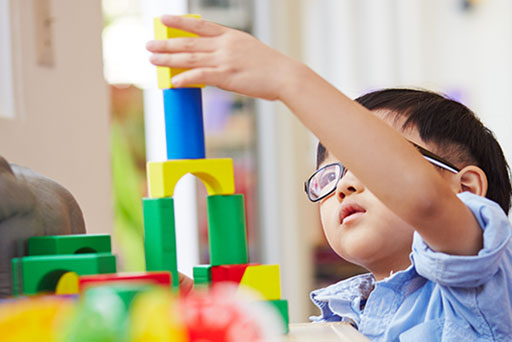 Young boy with glasses carefully building with colorful blocks.