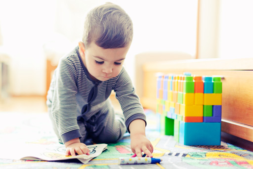Young boy in pajamas playing with blocks and coloring at home.