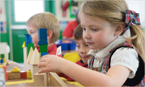 Little girl building with blocks in Primrose Schools classroom.