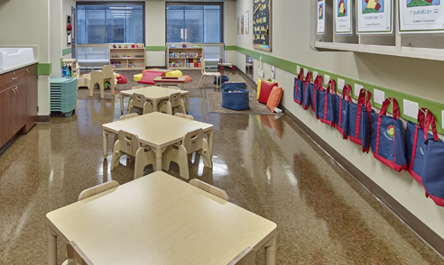 Employer-sponsored child care classroom with kids' tables, play area and bookbags hanging on wall.