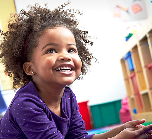 Young girl with curly hair, smiling in a Primrose School classroom.